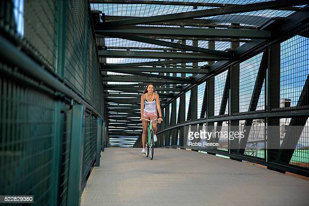 a young, happy adult woman riding her bicycle on an urban bridge - robb reece stock pictures, royalty-free photos & images