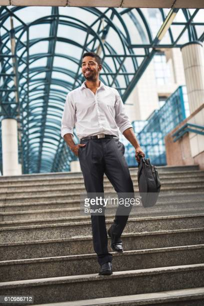 Young happy African American businessman moving down the stairs.