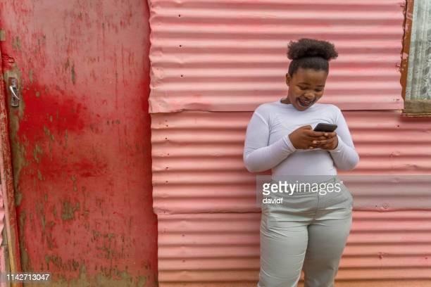 young happy african woman using a mobile phone - província do cabo ocidental imagens e fotografias de stock