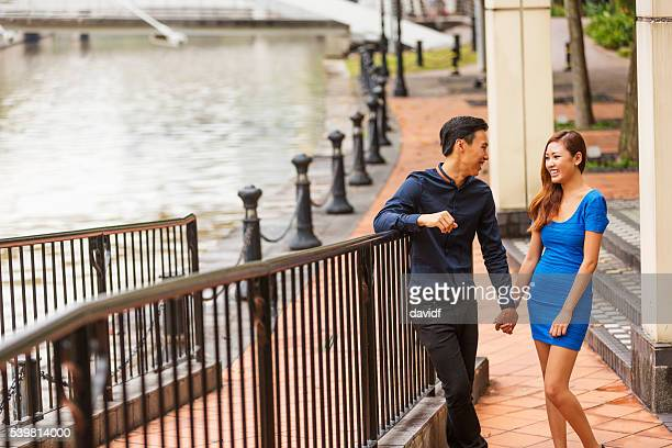 Young Happy Asian Couple Walking Together by the Singapore River