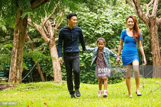 Joven familia feliz asiática caminar juntos en el parque