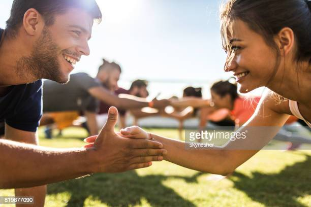 Young happy athletes cooperating while exercising on a sports training.