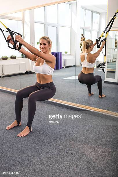 Young happy athletic woman exercising on Pilates exercise equipment.