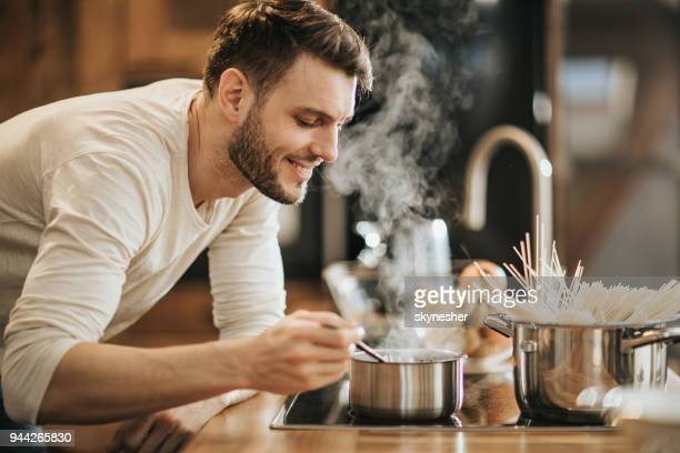 young happy bachelor enjoying in the smell of his cooking. - preparing food stock pictures, royalty-free photos & images