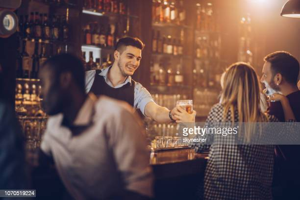 young happy bartender serving beer to his customers in a bar. - bartender stock pictures, royalty-free photos & images