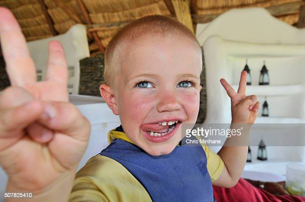Young happy beautiful boy using fingers for peace sign with tongue sticking out.