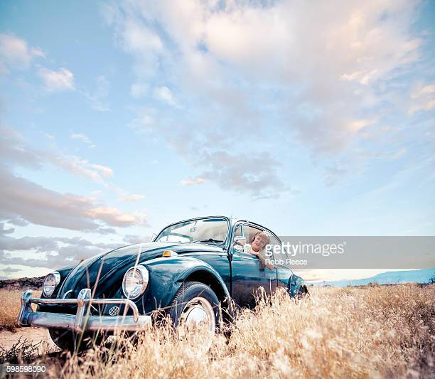 a young, happy boy sitting in a 1967 vintage volkswagen bug - robb reece stock pictures, royalty-free photos & images