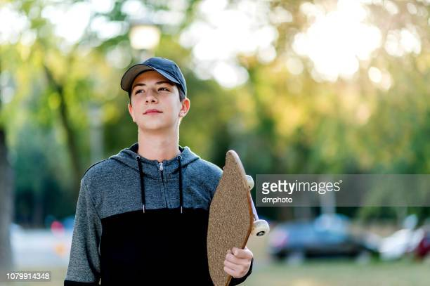 young happy boy with skateboard on the park - one teenage boy only stock pictures, royalty-free photos & images