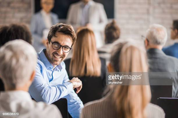 young happy businessman attending a training class in a board room. - attending stock pictures, royalty-free photos & images