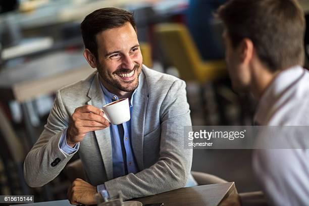 young happy businessman drinking coffee and talking to his colleague. - pausa para o café - fotografias e filmes do acervo