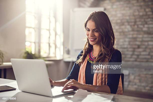 Young happy businesswoman working on laptop in the office.