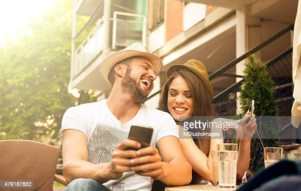 Young happy couple at cafe using smartphone