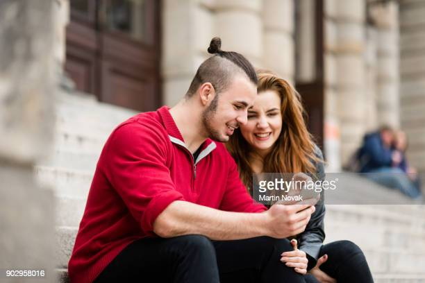 Young happy couple browsing videos on mobile