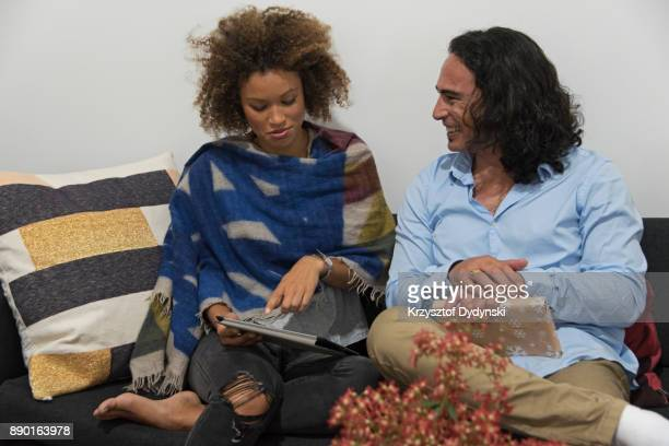 SYD112017  Young happy couple chatting in lounge room