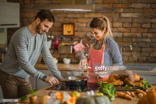 jovem casal feliz cooperando ao cozinhar o prato para o jantar de ação de graças. - preparação - fotografias e filmes do acervo