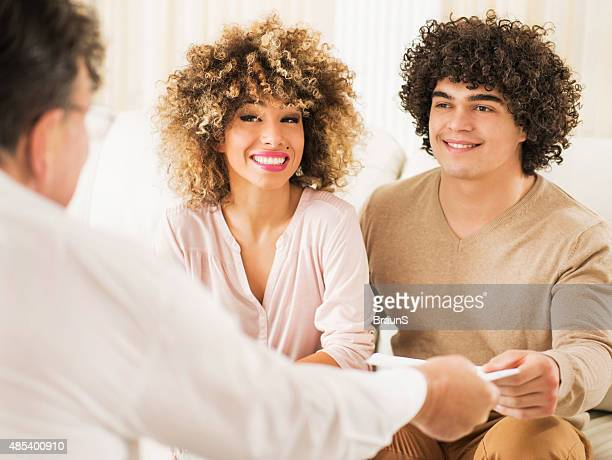 Young happy couple cooperating with their real estate agent.