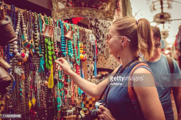 young happy couple discover gifts market while travelling - street market stock pictures, royalty-free photos & images