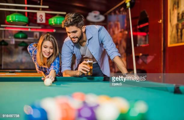junge glückliche paar genießen eine pool-spiel in einer kneipe - poolbillard billard stock-fotos und bilder