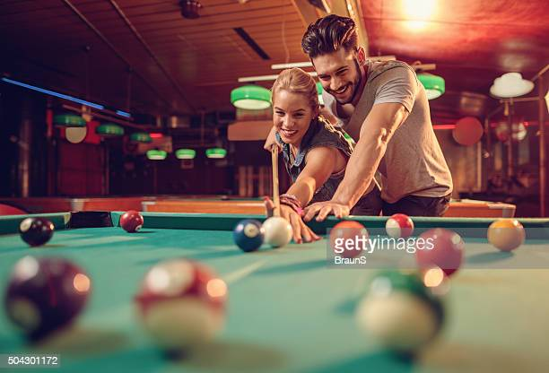Young happy couple enjoying in a billiard game together.