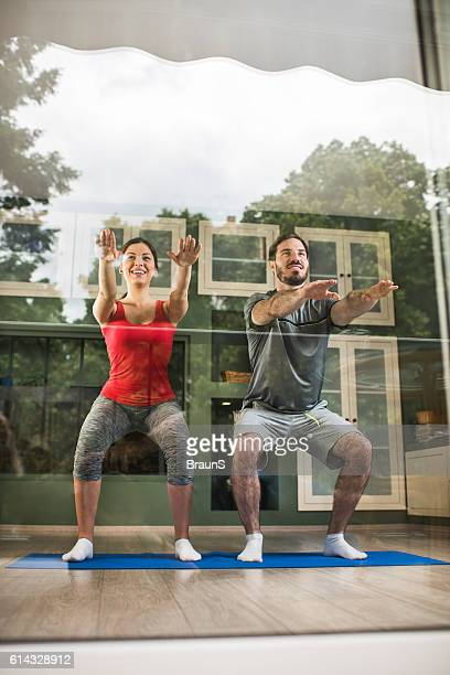 Young happy couple exercising squats together at home.