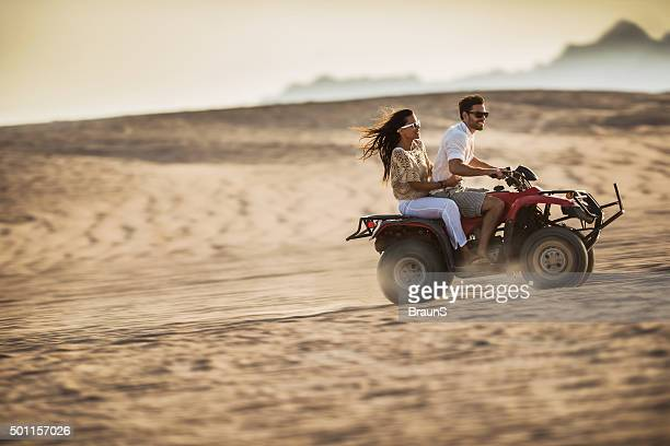 Young happy couple having fun while driving on quad bike.