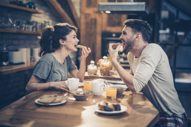 young happy couple having fun while eating sandwiches for breakfast in the kitchen. - couples romance stock pictures, royalty-free photos & images