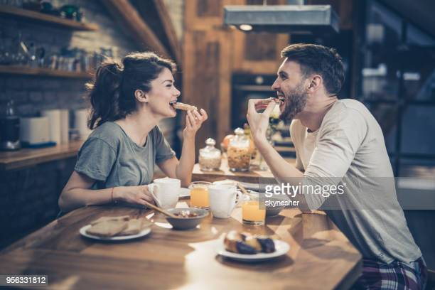 young happy couple having fun while eating sandwiches for breakfast in the kitchen. - dating stock pictures, royalty-free photos & images