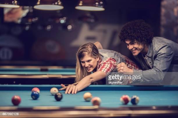 若い幸せなカップルがビリヤードを再生しながら楽しい時を過します。