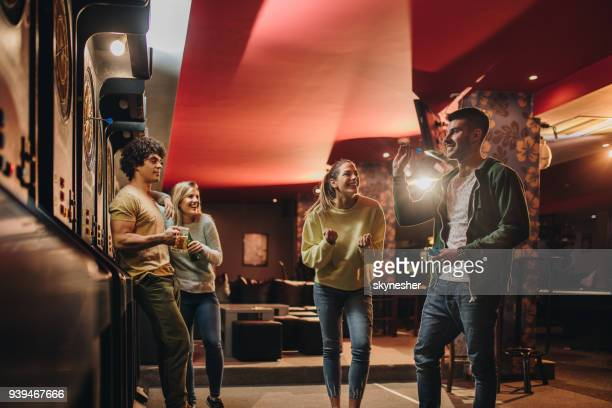 Young happy couple having fun with their friends while playing darts in a pub.