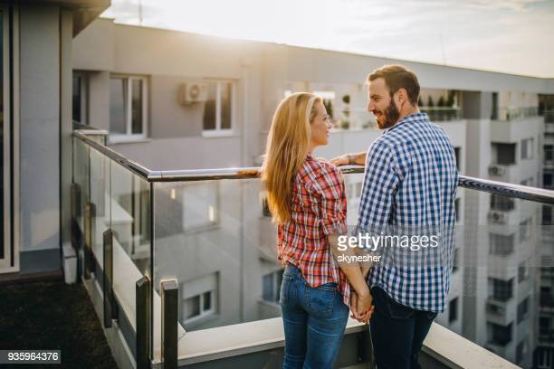 young happy couple holding hands and talking on a penthouse terrace, - balcony stock pictures, royalty-free photos & images