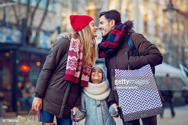 young, happy couple is kissing after shopping at christmas - saldi foto e immagini stock