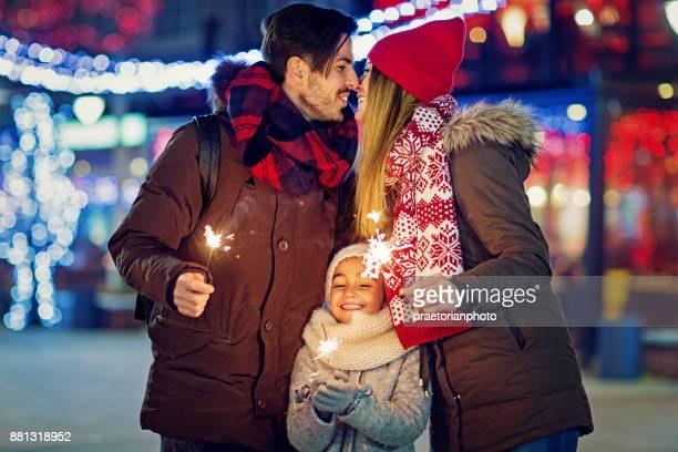 Jong, gelukkige paar is zoenen en houden van vuurwerk op Kerstmis