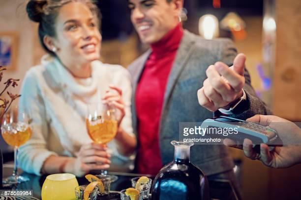 Young, glückliches Paar in der Bar mit einer Smartwatch zahlt sich
