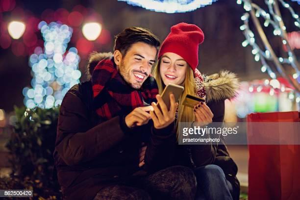 Jeune, couple heureux est le shopping en ligne en utilisant leur téléphone portable et une carte de crédit à Noël.