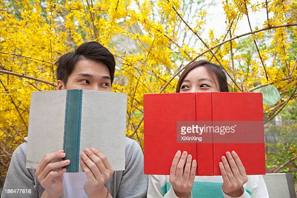 Young happy couple looking at each other over the top of their books, outdoors in spring