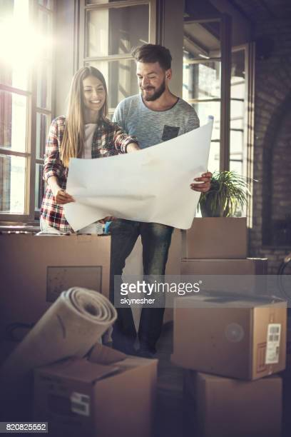 young happy couple looking at renovation plans at their new home. - reform stock pictures, royalty-free photos & images