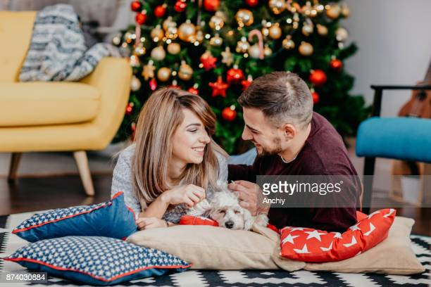 Young happy couple lying on pillows in front of Christmas tree