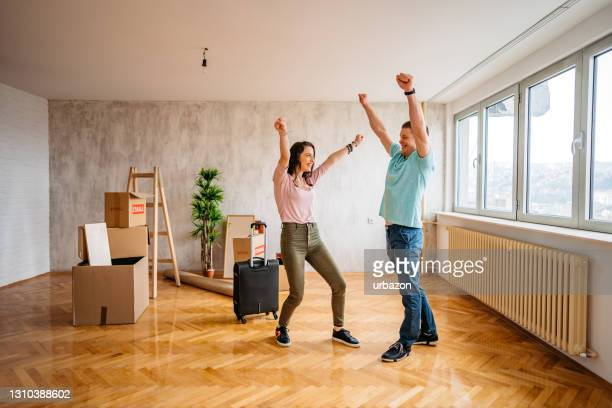 young happy couple moving in new apartment with joy - mortgage stock pictures, royalty-free photos & images