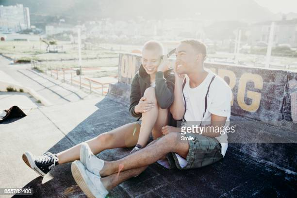 Young happy couple on rooftop sharing headphones