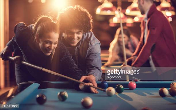 Young happy couple playing billiard in a pool hall.