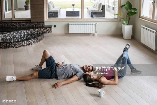 Young happy couple relaxing on a parquet floor at their new apartment.