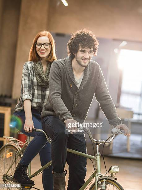 Young happy couple riding a tandem bike indoors.