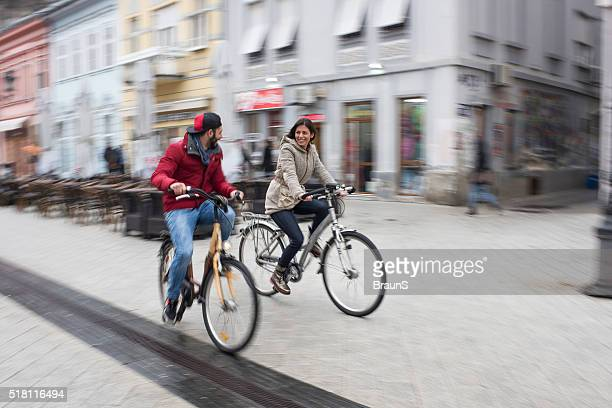Young happy couple riding bikes in blurred motion.