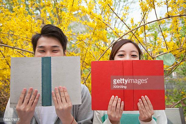 Young happy couple sitting side by side and reading their books, face partially obstructed, outdoors in springtime