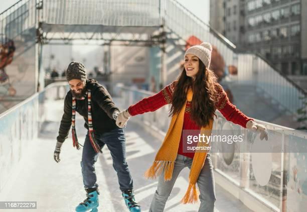 junges glückliches paar skatet zusammen - schlittschuh stock-fotos und bilder