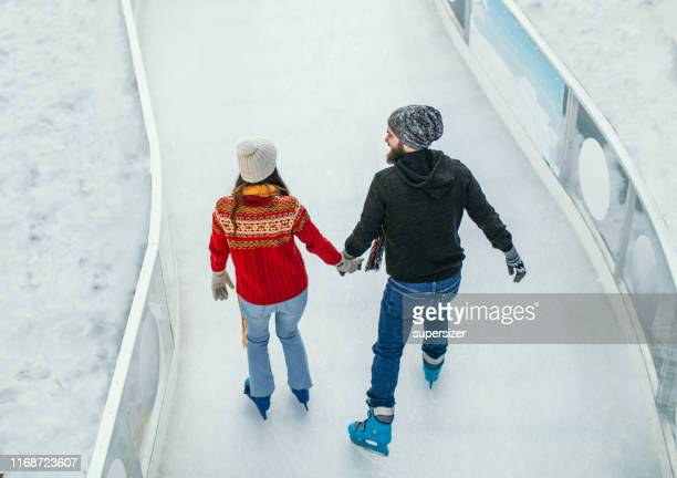 young happy couple skating together - ice rink stock pictures, royalty-free photos & images