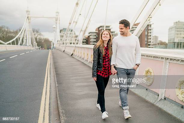 young happy couple strolling on bridge, battersea park, london, uk - battersea park stock pictures, royalty-free photos & images
