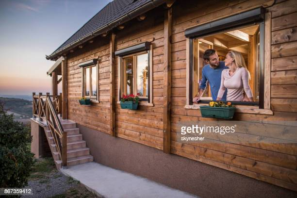 Young happy couple talking on a window of their chalet.