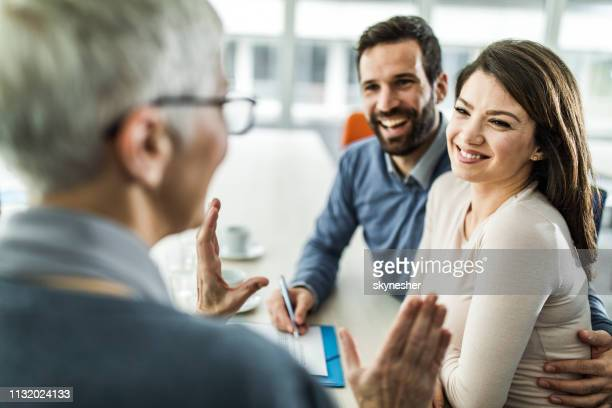 young happy couple talking to their insurance agent on a meeting in the office - bank customer stock pictures, royalty-free photos & images