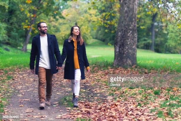 Young happy couple walking in the autumn park